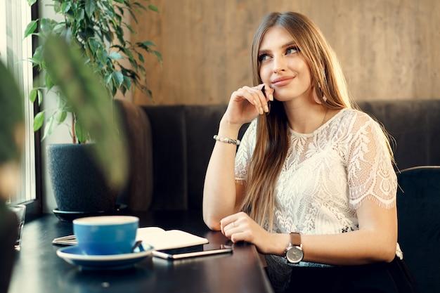 Jonge zakenvrouw zitten aan de tafel in een coffeeshop en het maken van aantekeningen