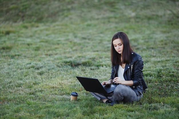 Jonge zakenvrouw zitten en werken in park met laptop