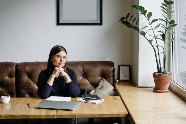 Jonge zakenvrouw zittend aan tafel en het maken van notities in notitieblok.