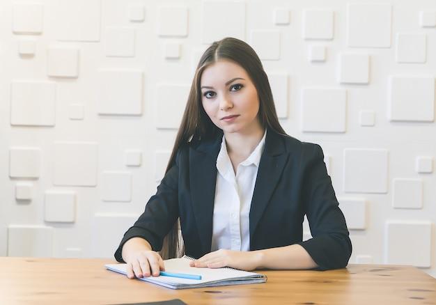 Jonge zakenvrouw zittend aan tafel, verzonken in gedachten, vermoeid kijkend naar de camera, tegen een witte muur achtergrond
