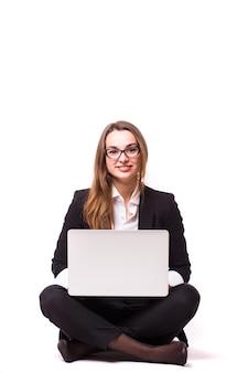 Jonge zakenvrouw zittend op de vloer en met behulp van laptop geïsoleerd op een witte muur