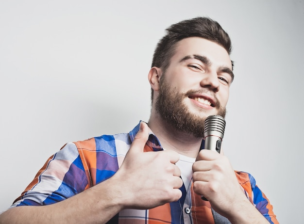 Jonge zanger man met microfoon over grijze achtergrond