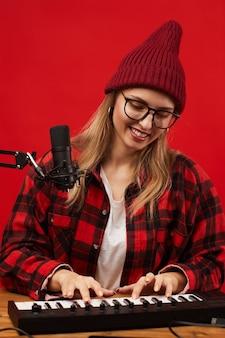 Jonge zangeres in brillen en in vrijetijdskleding spelen op muzikaal toetsenbord en het schrijven van een lied zittend aan tafel