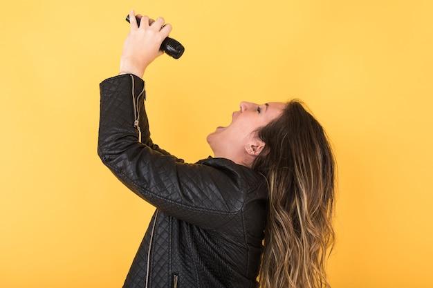 Jonge zangeres meisje draagt zwart lederen jas zingen met microfoon op geel.