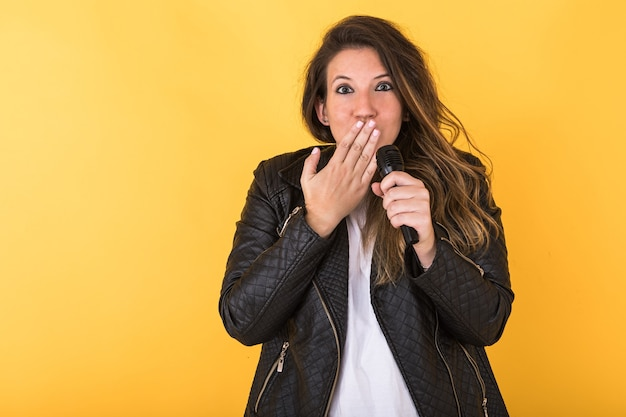 Jonge zangeres meisje, gekleed in zwart lederen jas en microfoon, verrassing gebaar maken op geel.