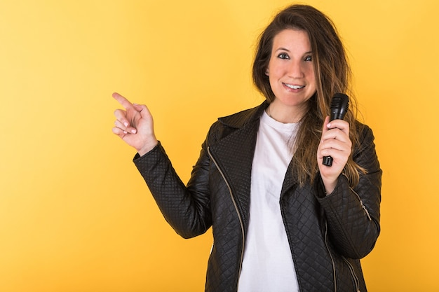 Jonge zangeres meisje, gekleed in zwart lederen jas en microfoon, wijzend met haar rechterhand op geel.