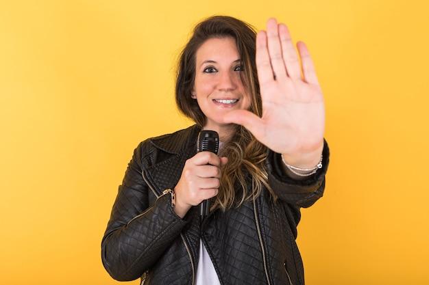 Jonge zangeres meisje, gekleed in zwart leren jas en microfoon, maakt het stop-teken met haar hand, op geel.