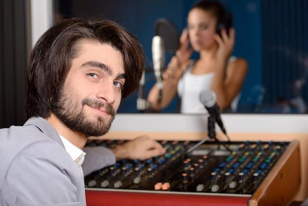 Jonge zangeres met studiotechnicus.