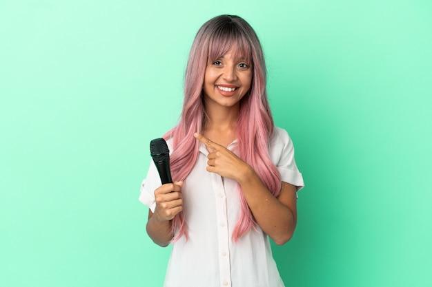 Jonge zangeres van gemengd ras met roze haar geïsoleerd op een groene achtergrond die naar de zijkant wijst om een product te presenteren