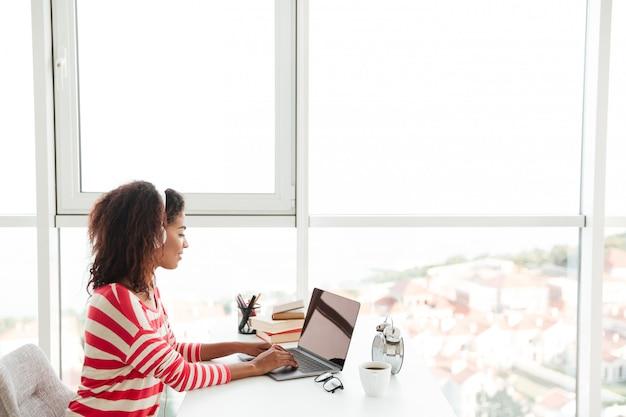 Jonge zekere afrikaanse vrouw die in hoofdtelefoons aan laptop werkt