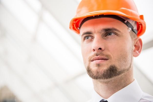 Jonge zekere architect met helm in het kantoor.