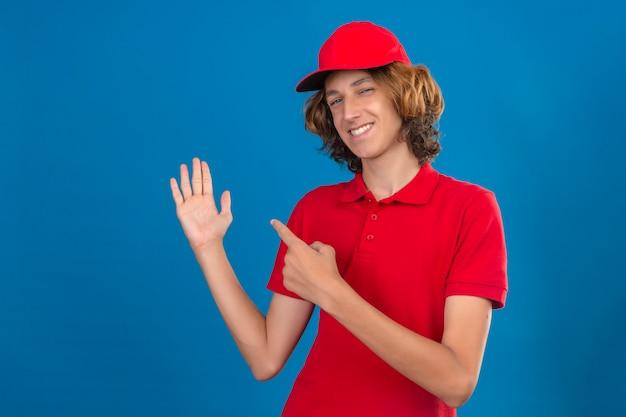 Jonge zekere leveringsmens in het rode eenvormige glimlachen zeker het richten met hand en vinger aan de kant over geïsoleerde blauwe muur