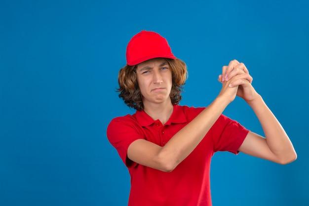 Jonge zekere leveringsmens in rode eenvormige status met een gebaar van groepswerk over geïsoleerde blauwe muur