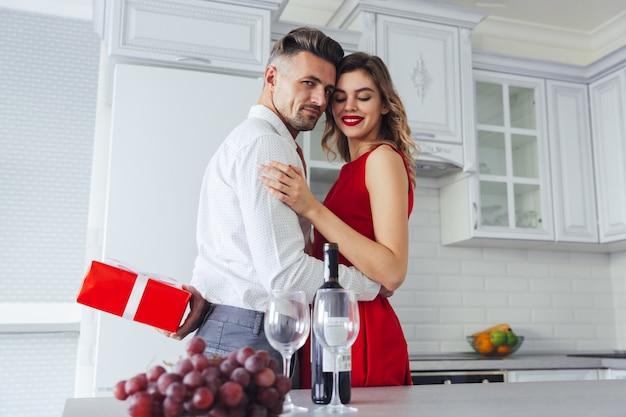 Jonge zekere man terwijl verbergen huidig voor zijn mooie vrouw, het concept van de valentijnskaartendag