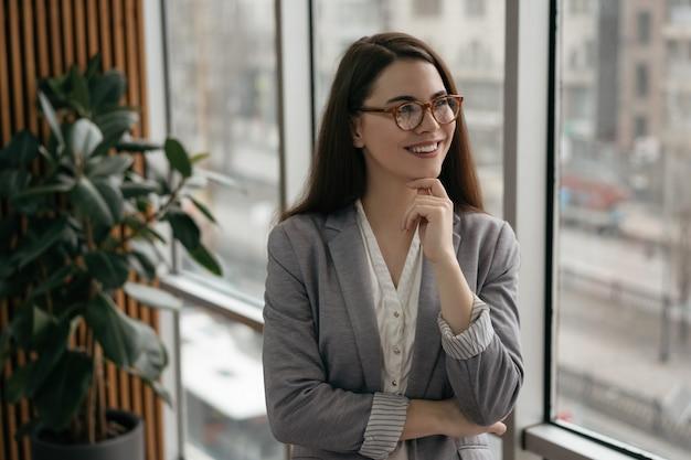 Jonge zekere manager die zich in bureau dichtbij venster bevindt, het glimlachen
