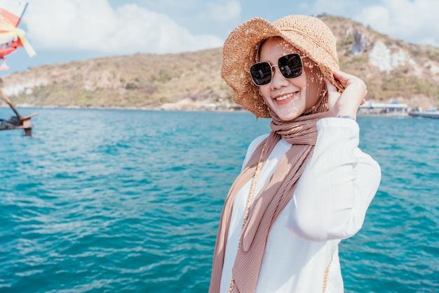 Jonge zekere moslimvrouw witte kleding op kust.