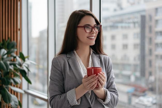 Jonge zekere onderneemster die zich in bureau dichtbij venster bevinden, kop van koffie houden en glimlachen