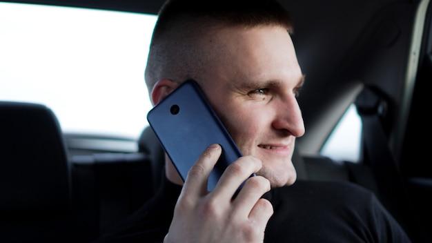 Jonge zekere zakenman die op mobiele telefoon spreekt