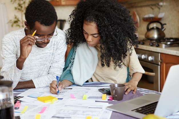 Jonge zelfverzekerde afrikaanse huisvrouw met afro kapsel helpt haar man om de binnenlandse financiën te beheren, te berekenen en notities te maken met pen, beide zittend aan de keukentafel met laptop en papieren