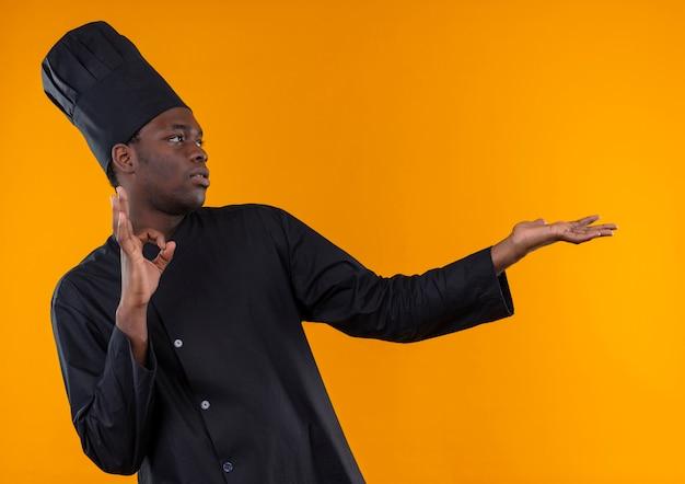 Jonge zelfverzekerde afro-amerikaanse kok in chef-kok uniform gebaren ok handteken en punten aan de zijkant geïsoleerd op oranje ruimte met kopie ruimte