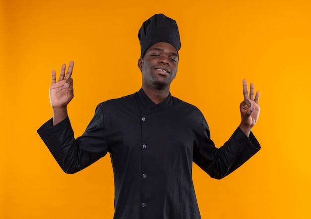 Jonge zelfverzekerde afro-amerikaanse kok in chef-kok uniforme gebaren okmhand bord met beide handen geïsoleerd op een oranje achtergrond met kopie ruimte