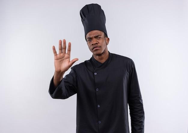 Jonge zelfverzekerde afro-amerikaanse kok in chef-kok uniforme gebaren stoppen handteken geïsoleerd op een witte achtergrond met kopie ruimte