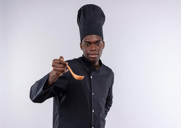 Jonge zelfverzekerde afro-amerikaanse kok in uniform chef houdt houten lepel en kijkt naar camera op wit met kopie ruimte