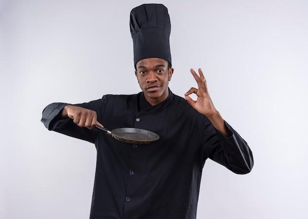 Jonge zelfverzekerde afro-amerikaanse kok in uniform chef houdt koekenpan en gebaren ok handteken geïsoleerd op een witte achtergrond met kopie ruimte