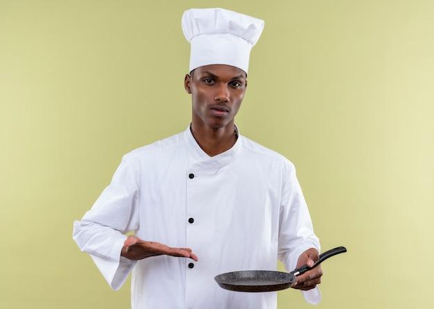 Jonge zelfverzekerde afro-amerikaanse kok in uniform chef houdt koekenpan en punten met hand geïsoleerd op groene achtergrond met kopie ruimte