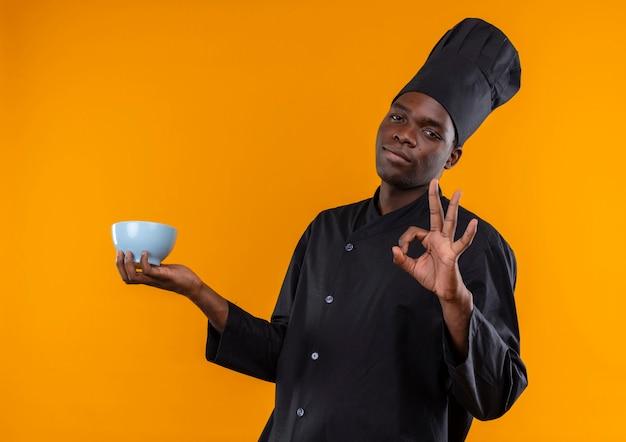Jonge zelfverzekerde afro-amerikaanse kok in uniform chef houdt kom en gebaren ok handteken op oranje met kopie ruimte