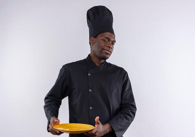 Jonge zelfverzekerde afro-amerikaanse kok in uniform chef houdt plaat en kijkt naar de camera op wit met kopie ruimte