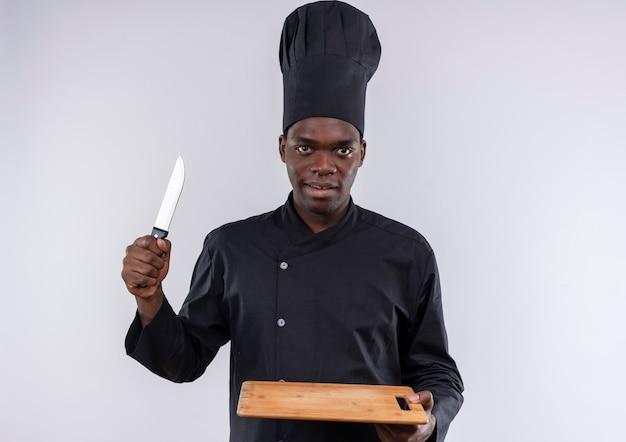 Jonge zelfverzekerde afro-amerikaanse kok in uniform chef houdt snijplank en mes op wit met kopie ruimte