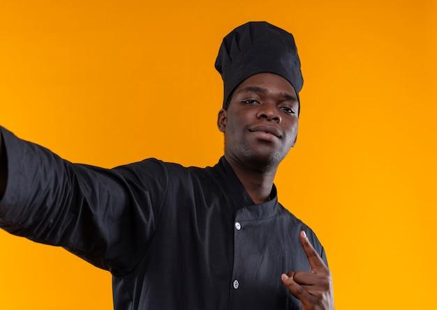 Jonge zelfverzekerde afro-amerikaanse kok in uniform chef-kok beweert camera vast te houden en gebaren hoorns handteken op oranje met kopie ruimte