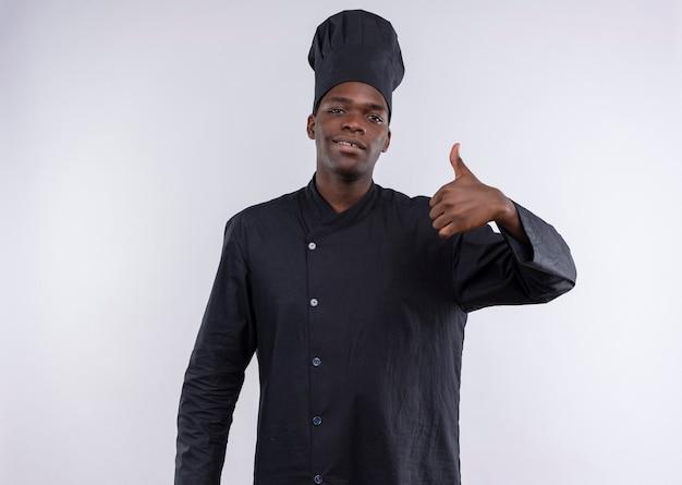 Jonge zelfverzekerde afro-amerikaanse kok in uniform chef-kok duimen omhoog en kijkt naar de camera op wit met kopie ruimte