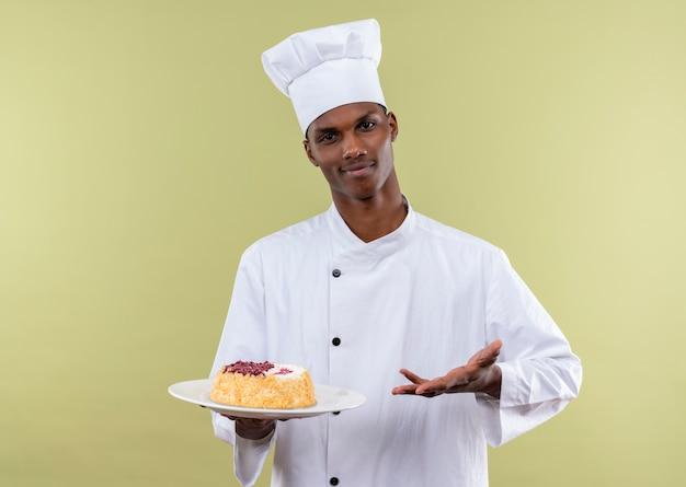 Jonge zelfverzekerde afro-amerikaanse kok in uniform chef-kok houdt cake op plaat en punten met hand geïsoleerd op groene achtergrond met kopie ruimte