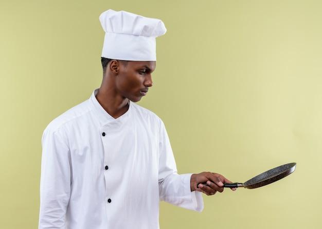 Jonge zelfverzekerde afro-amerikaanse kok in uniform chef-kok houdt en kijkt naar koekenpan geïsoleerd op groene achtergrond met kopie ruimte