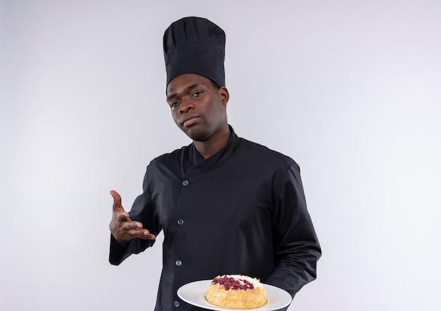 Jonge zelfverzekerde afro-amerikaanse kok in uniform chef-kok houdt en wijst naar cake op plaat camera kijken op wit met kopie ruimte