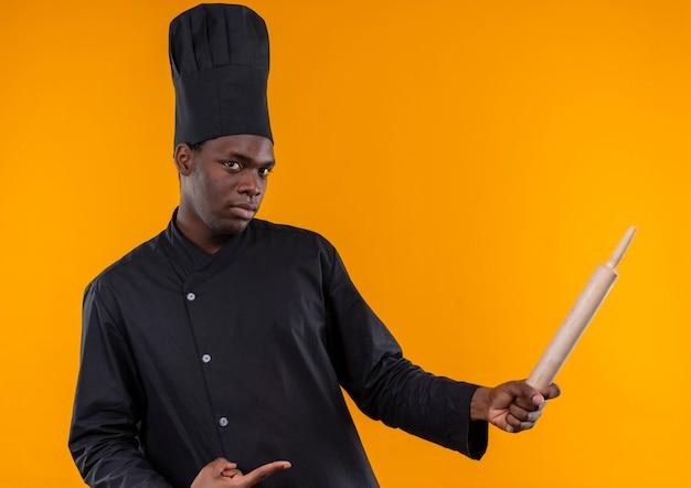 Jonge zelfverzekerde afro-amerikaanse kok in uniform chef-kok houdt en wijst op deegroller geïsoleerd op een oranje achtergrond met kopie ruimte