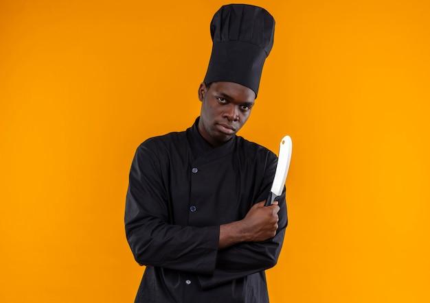 Jonge zelfverzekerde afro-amerikaanse kok in uniform chef-kok kruist armen en houdt mes op oranje met kopie ruimte