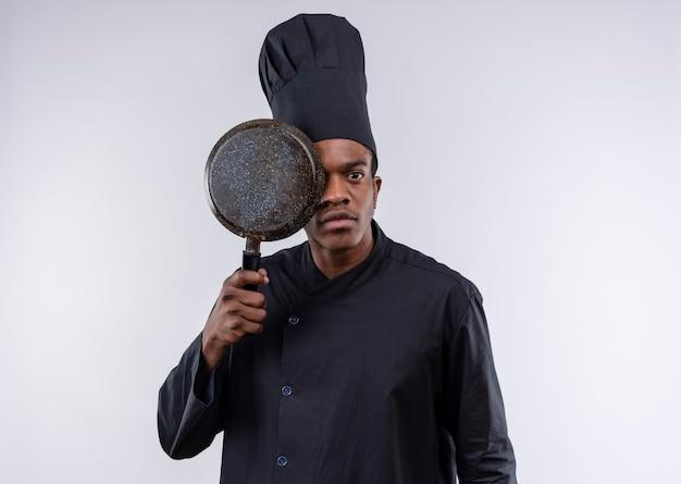 Jonge zelfverzekerde afro-amerikaanse kok in uniform chef-kok sluit oog met koekenpan geïsoleerd op een witte achtergrond met kopie ruimte