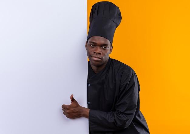 Jonge zelfverzekerde afro-amerikaanse kok in uniform chef staat achter de witte muur en duimen kijken naar camera op oranje met kopie ruimte