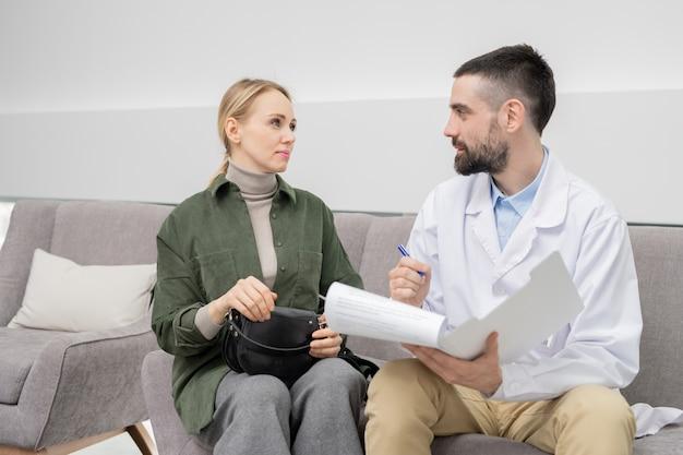Jonge zelfverzekerde arts in whitecoat maken van aantekeningen in document tijdens het raadplegen van een van zijn patiënten in de lounge van tandheelkundige klinieken