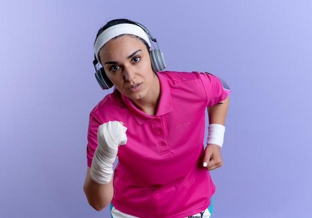 Jonge zelfverzekerde blanke sportieve vrouw met hoofdband en polsbandjes op koptelefoon pretendeert te rennen