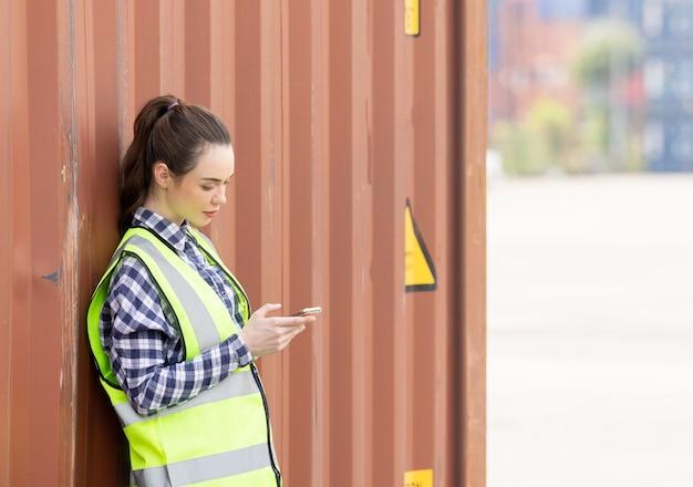 Jonge zelfverzekerde blanke vrouw ingenieur met behulp van mobiele telefoon en het dragen van groene veiligheidshelm en controleren op controle laden containers box van vrachtschip voor import en export