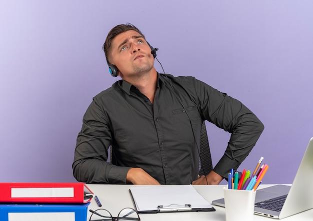 Jonge zelfverzekerde blonde kantoormedewerker man op koptelefoon zit aan bureau met office-hulpprogramma's met behulp van laptop opgezocht geïsoleerd op violette ruimte met kopie ruimte