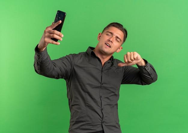 Jonge zelfverzekerde blonde knappe man kijkt naar telefoon en wijst naar zichzelf nemen selfie geïsoleerd op groene ruimte met kopie ruimte