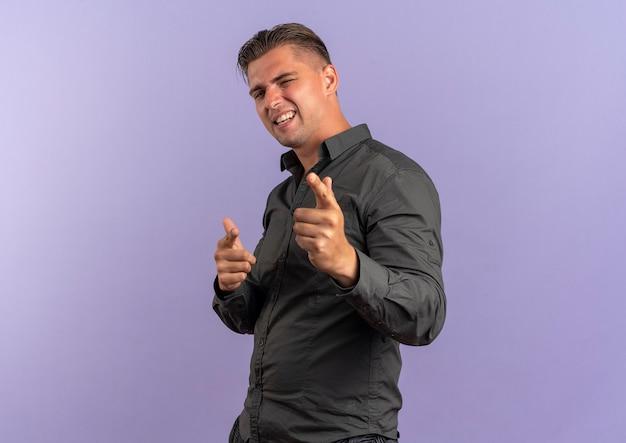 Jonge zelfverzekerde blonde knappe man knippert met oog en wijst naar camera geïsoleerd op violette achtergrond met kopie ruimte