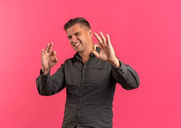 Jonge zelfverzekerde blonde knappe man knippert oog en gebaren ok handteken geïsoleerd op roze achtergrond met kopie ruimte