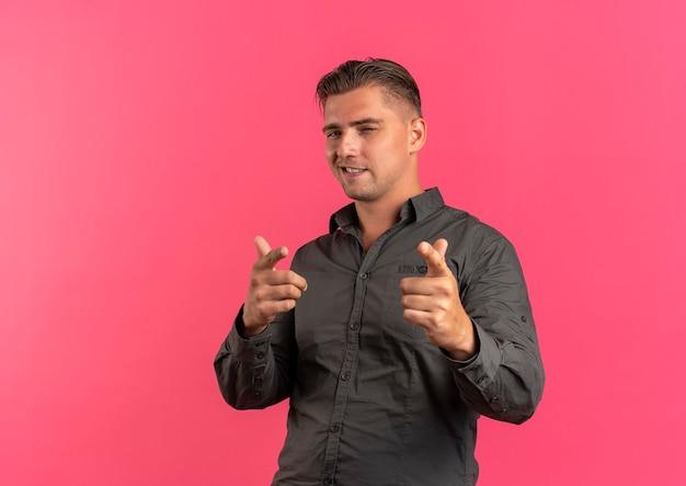 Jonge zelfverzekerde blonde knappe man knippert oog en wijst naar camera geïsoleerd op roze achtergrond met kopie ruimte