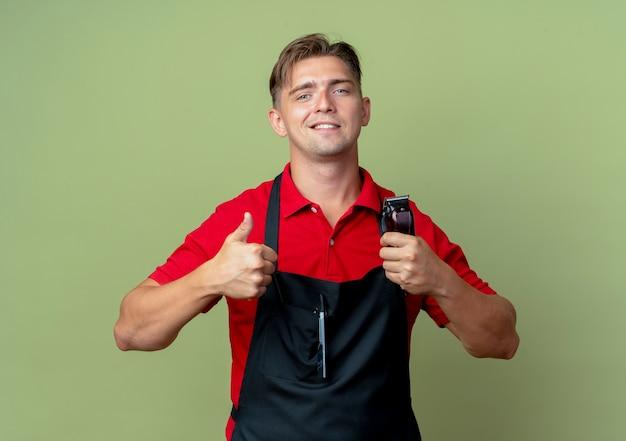 Jonge zelfverzekerde blonde mannelijke kapper in uniform duimen omhoog en houdt haartrimmer geïsoleerd op olijfgroen ruimte met kopie ruimte